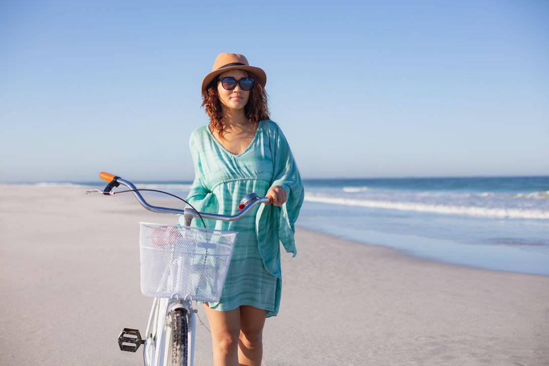 Front view of beautiful mixed race woman with bicycle walking on beach in the sunshine