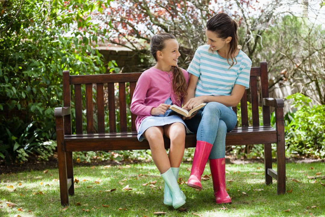 Cheerful mother and daughter reading novel while sitting on wooden bench at backyard Free Stock Images from PikWizard