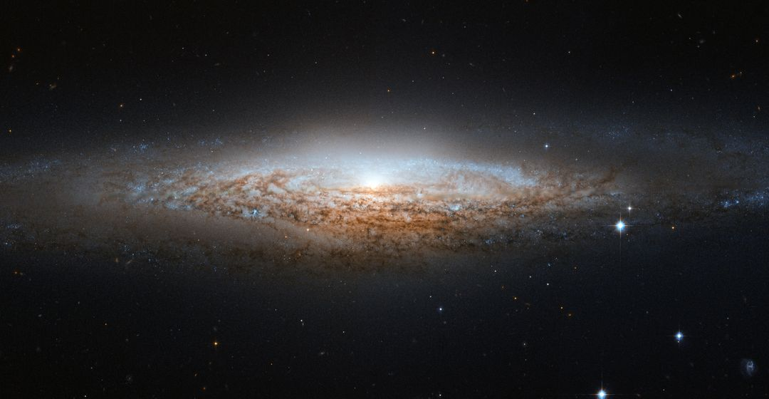 "The Hubble Space Telescope has spotted a UFO — well, the UFO Galaxy, to be precise. NGC 2683 is a spiral galaxy seen almost edge-on, giving it the shape of a classic science fiction spaceship. This is why the astronomers at the Astronaut Memorial Planetarium and Observatory gave it this attention-grabbing nickname. While a bird's eye view lets us see the detailed structure of a galaxy (such as this Hubble image of a barred spiral), a side-on view has its own perks. In particular, it gives astronomers a great opportunity to see the delicate dusty lanes of the spiral arms silhouetted against the golden haze of the galaxy's core. In addition, brilliant clusters of young blue stars shine scattered throughout the disc, mapping the galaxy's star-forming regions. Perhaps surprisingly, side-on views of galaxies like this one do not prevent astronomers from deducing their structures. Studies of the properties of the light coming from NGC 2683 suggest that this is a barred spiral galaxy, even though the angle we see it at does not let us see this directly. NGC 2683, discovered on 5 February 1788 by the famous astronomer William Herschel, lies in the Northern constellation of Lynx. A constellation named not because of its resemblance to the feline animal, but because it is fairly faint, requiring the ""sensitive eyes of a cat"" to discern it. And when you manage to get a look at it, you'll find treasures like this, making it well worth the effort. This image is produced from two adjacent fields observed in visible and infrared light by Hubble's Advanced Camera for Surveys. A narrow strip which appears slightly blurred and crosses most the image horizontally is a result of a gap between Hubble's detectors. This strip has been patched using images from observations of the galaxy made by ground-based telescopes, which show significantly less detail. The field of view is approximately 6.5 by 3.3 arcminutes.  Credit: ESA/Hubble &amp; NASA  <b><a href=""http://www.nasa.gov/audience/formedia/features/MP_Photo_Guidelines.html"" rel=""nofollow"">NASA image use policy.</a></b>  <b><a href=""http://www.nasa.gov/centers/goddard/home/index.html"" rel=""nofollow"">NASA Goddard Space Flight Center</a></b> enables NASA's mission through four scientific endeavors: Earth Science, Heliophysics, Solar System Exploration, and Astrophysics. Goddard plays a leading role in NASA's accomplishments by contributing compelling scientific knowledge to advance the Agency's mission.  <b>Follow us on <a href=""http://twitter.com/NASA_GoddardPix"" rel=""nofollow"">Twitter</a></b>  <b>Like us on <a href=""http://www.facebook.com/pages/Greenbelt-MD/NASA-Goddard/395013845897?ref=tsd"" rel=""nofollow"">Facebook</a></b>  <b>Find us on <a href=""http://instagrid.me/nasagoddard/?vm=grid"" rel=""nofollow"">Instagram</a></b>"