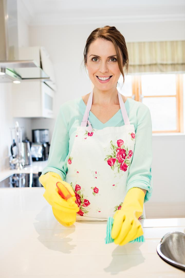 Portrait of happy woman working in kitchen at home