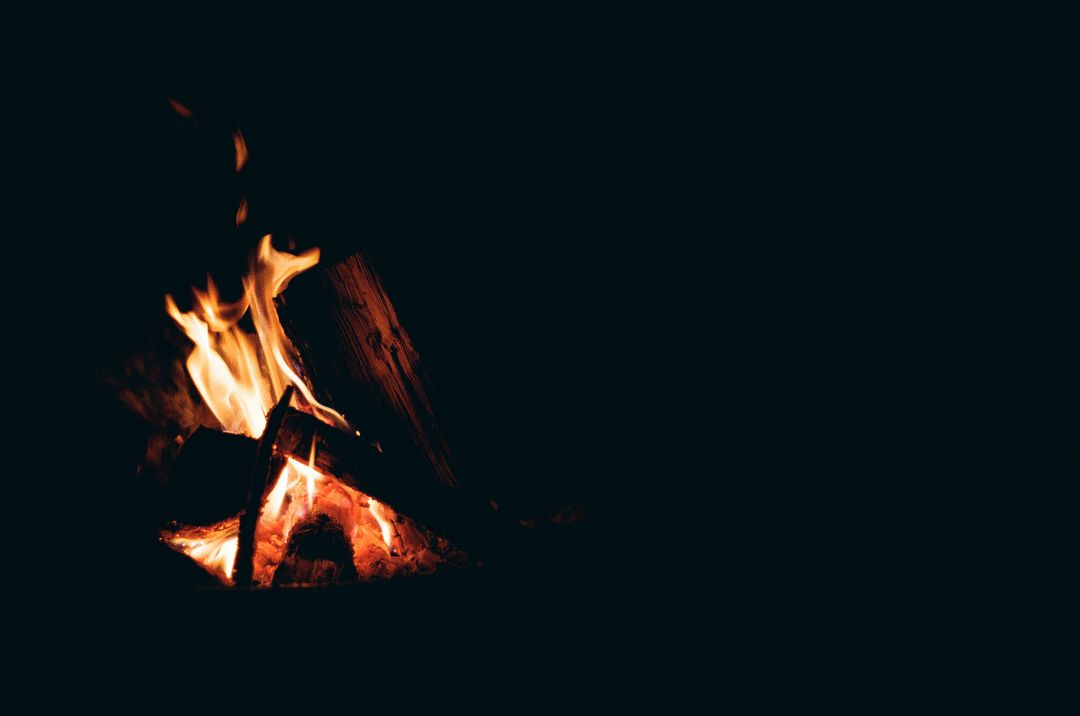 Small burning pile of wood with black background