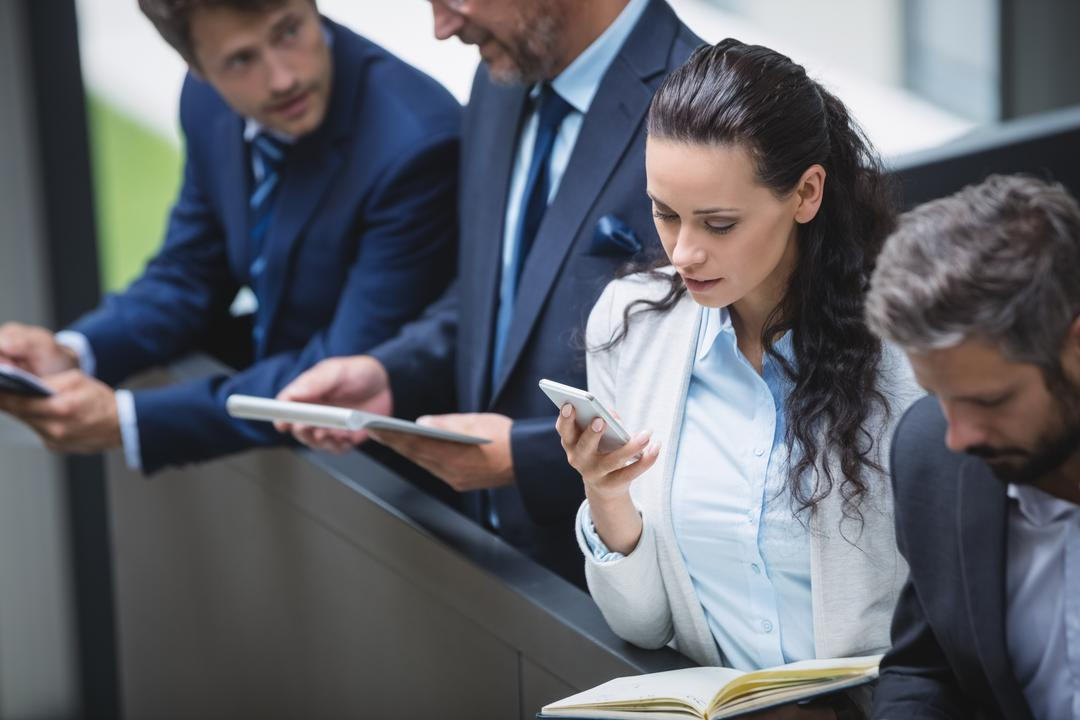 Businesspeople using mobile phone and digital tablet in office