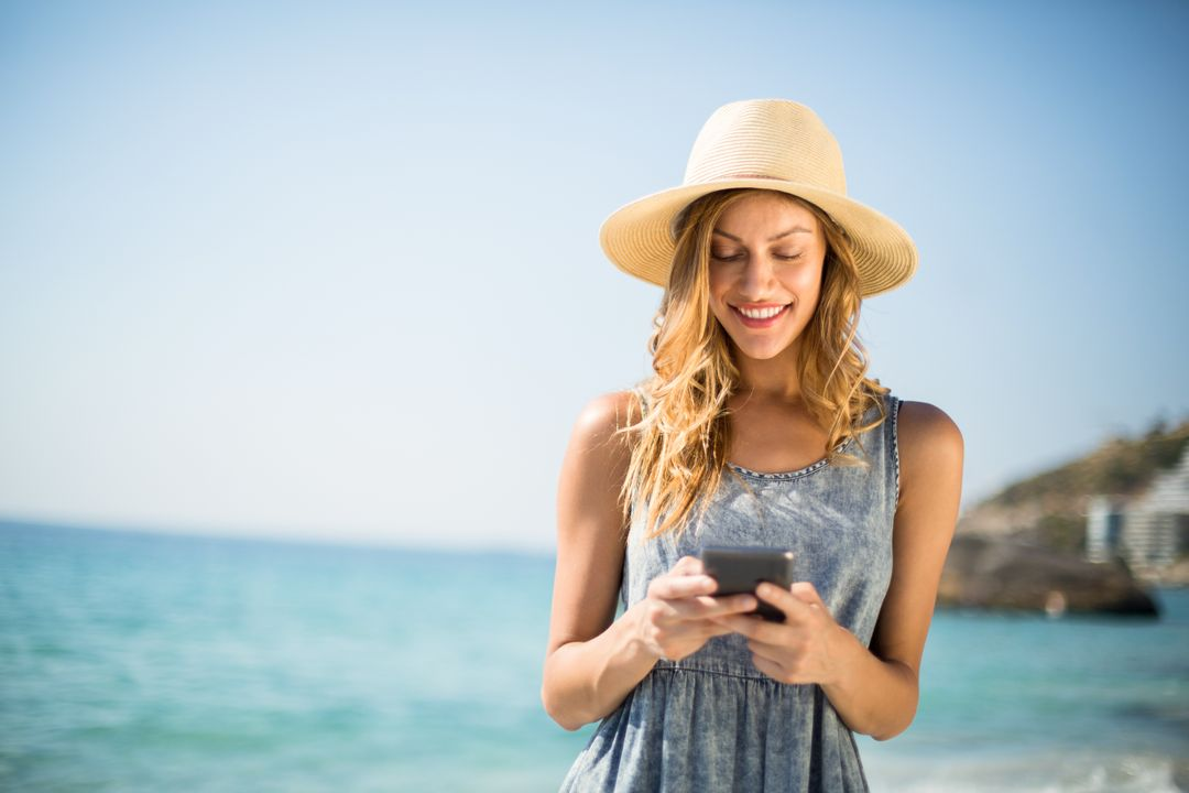 Young woman smiling while using mobile phone at beach on sunny day Free Stock Images from PikWizard