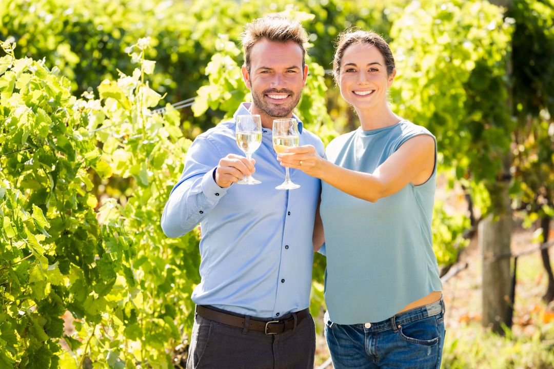Portrait of smiling young couple holding wineglasses at vineyard on sunny day