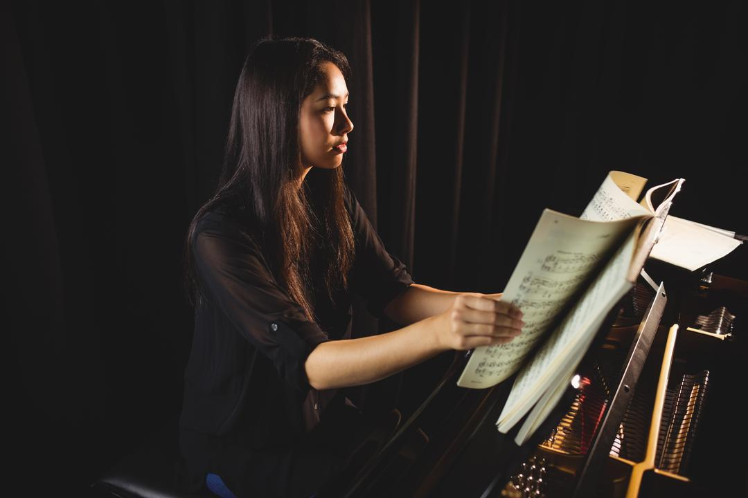 Female student looking at sheet music while playing a piano in a studio