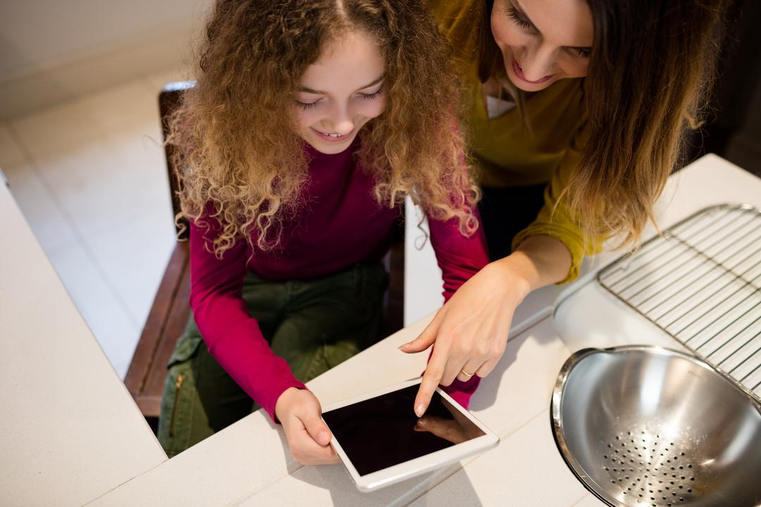 Mother and daughter using digital tablet in kitchen at home