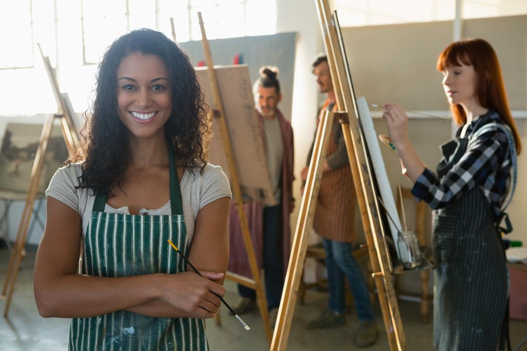Portrait of smiling female artist with friends painting in background at art class