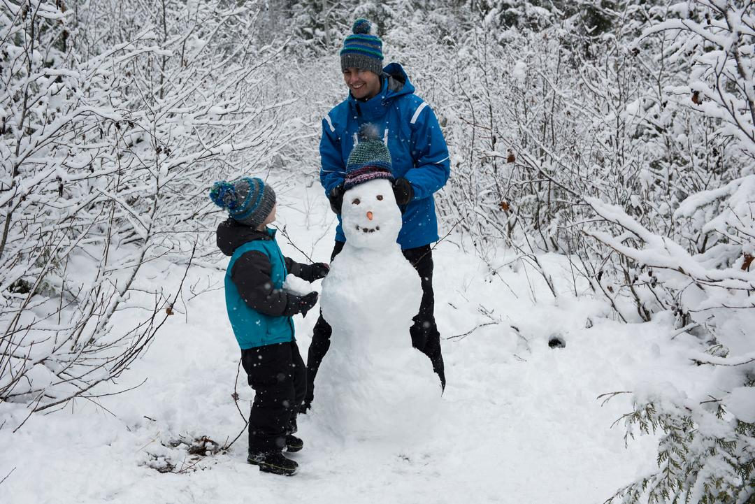 Father and son making snowman on snowy day