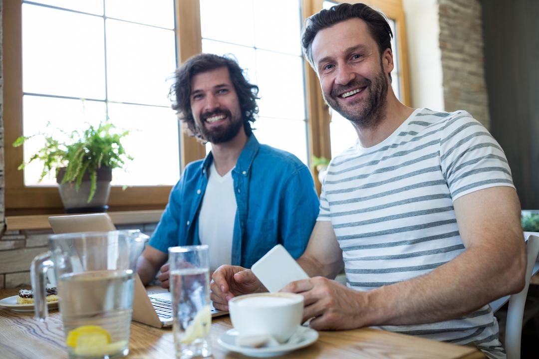 Portrait of two smiling men sitting at table in coffee shop