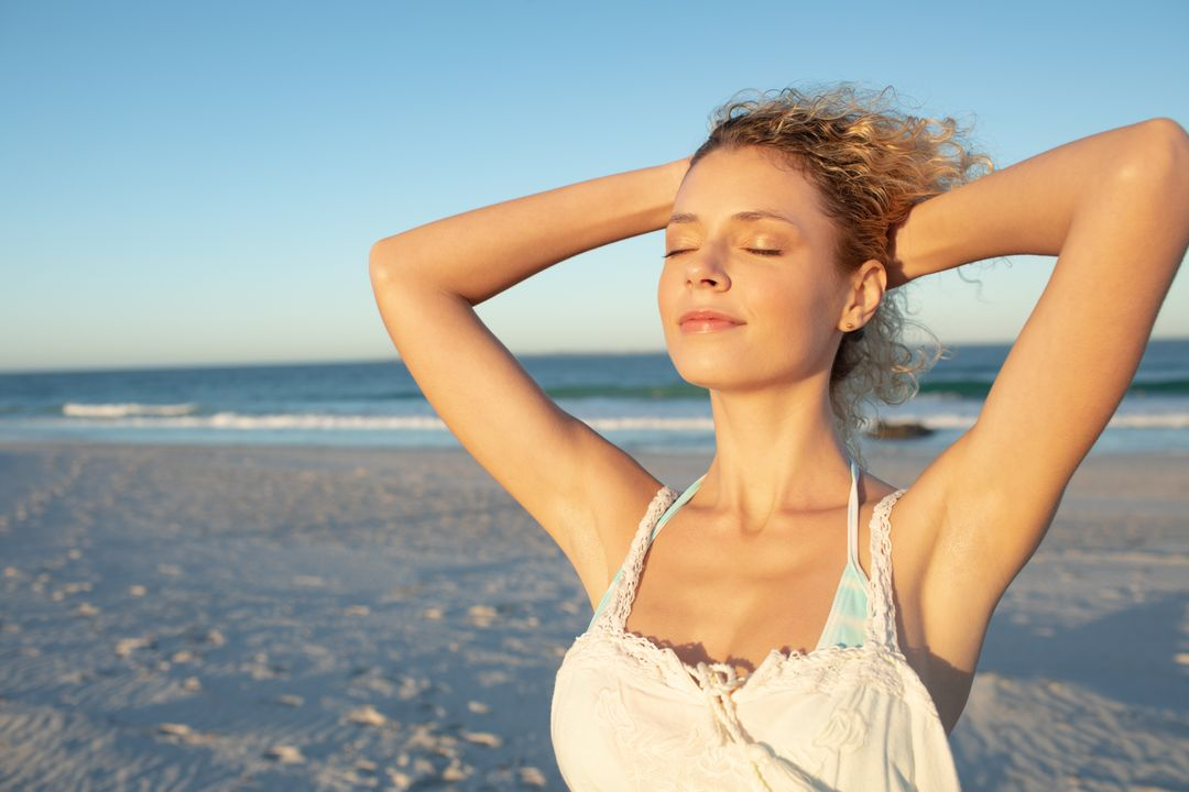 Beautiful woman standing with eyes closed on the beach Free Stock Images from PikWizard