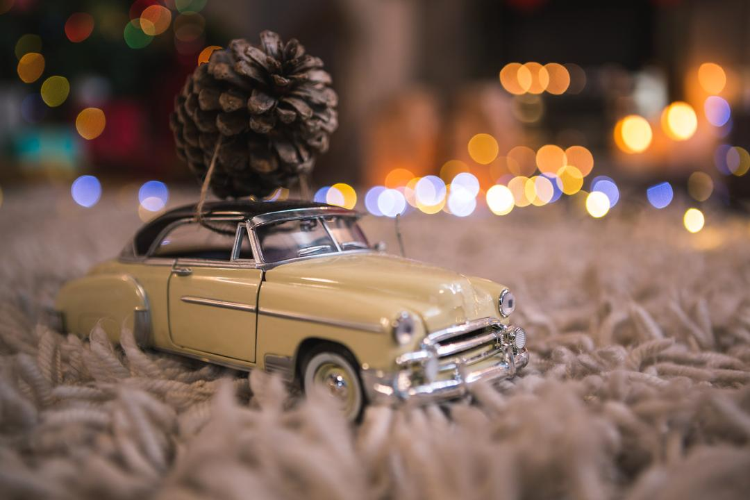 Toy car carrying christmas pine cone on fur carpet Free Stock Images from PikWizard