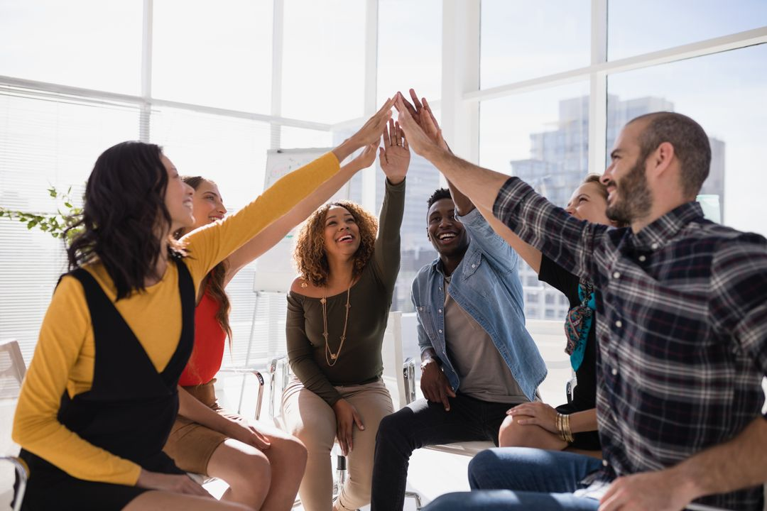 Group of happy executives giving high five to each other in office Free Stock Images from PikWizard