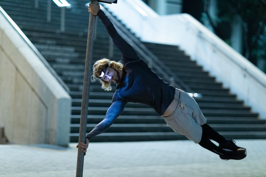 Front view of a fit Caucasian man with long blonde hair wearing sportswear exercising outdoors in the city at the evening, doing a human flag position on the street sign, wearing head light. Free Stock Images from PikWizard