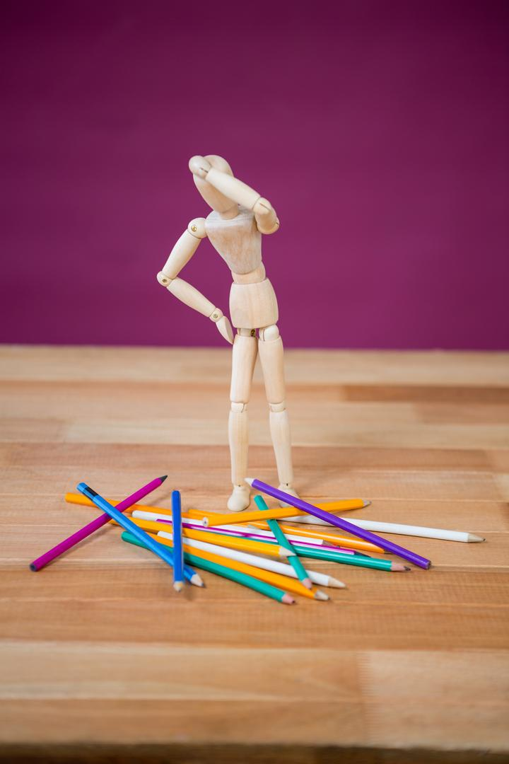 Conceptual image of figurine looking at pencil Free Stock Images from PikWizard