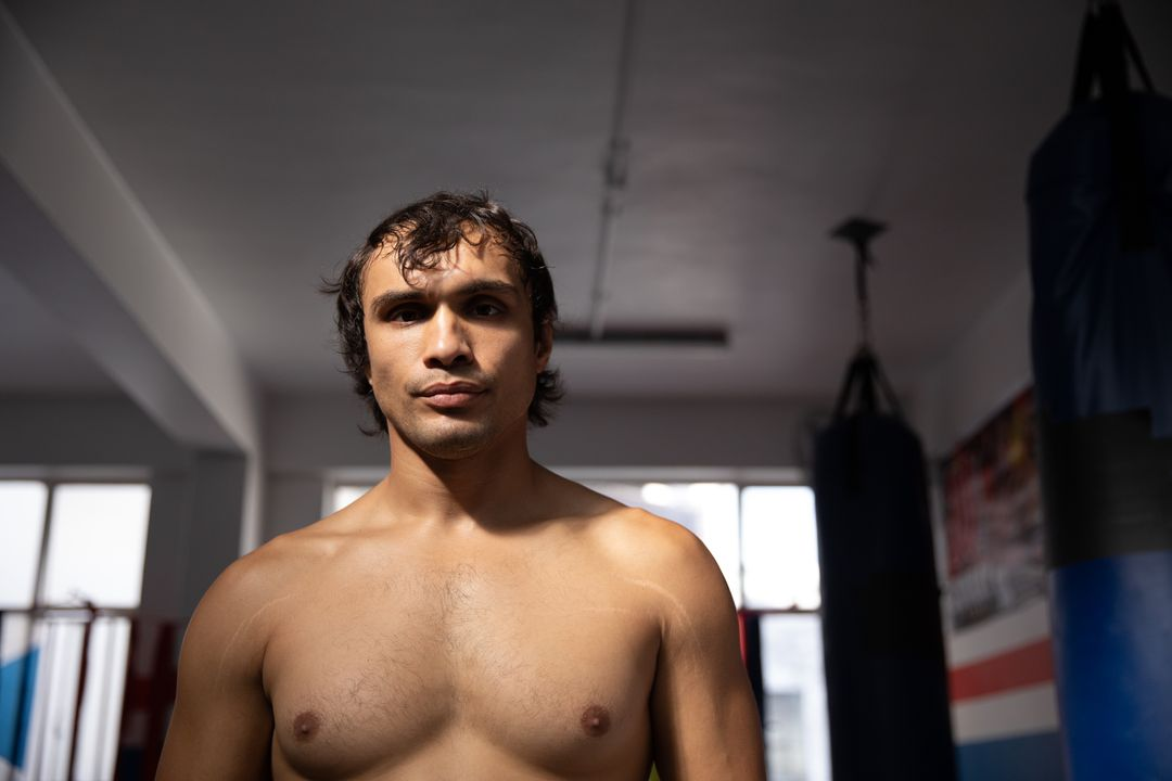 Portrait of a young mixed race male boxer with short dark hair, shirtless, in a boxing gym looking straight to the camera. Free Stock Images from PikWizard