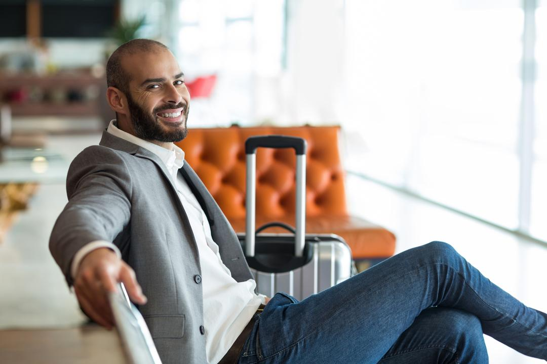 Portrait of smiling businessman sitting on chair in waiting area at the airport terminal