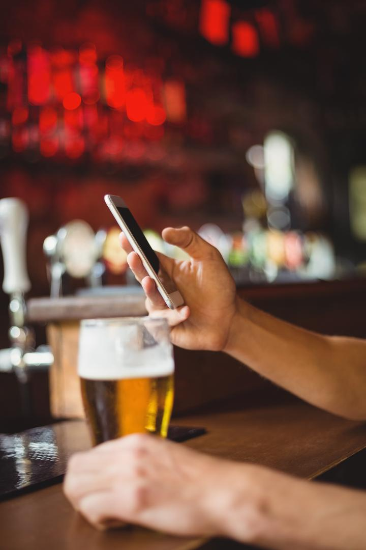 Man with glass of beer using mobile phone in counter at bar