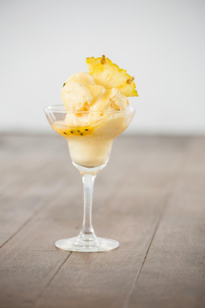 Cup of icecream decorated with a pineapple wedge