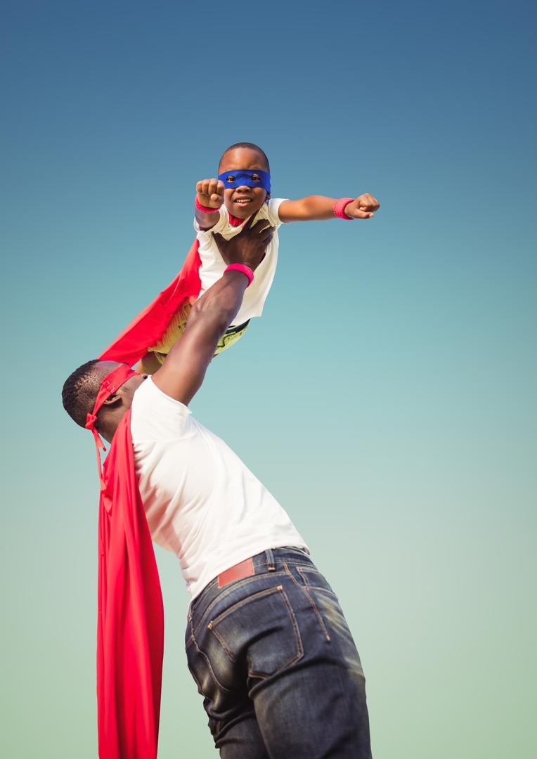 Digital composition of a man lifting kid in superhero costume