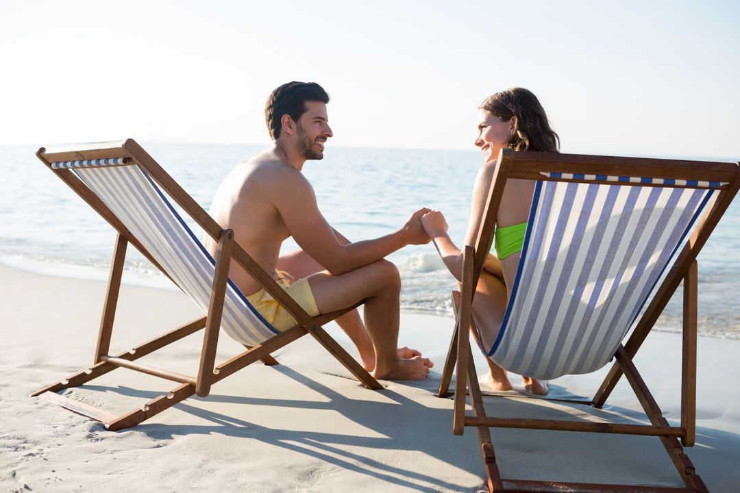 Happy couple holding hands while sitting on lounge chairs at beach during sunny day Free Stock Images from PikWizard