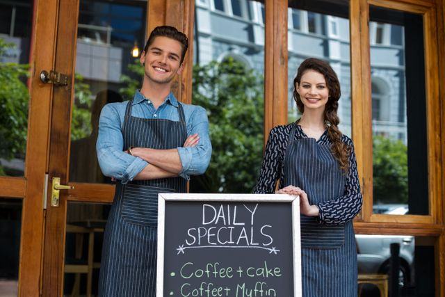 Waiter and waitress standing with menu board outside the cafe