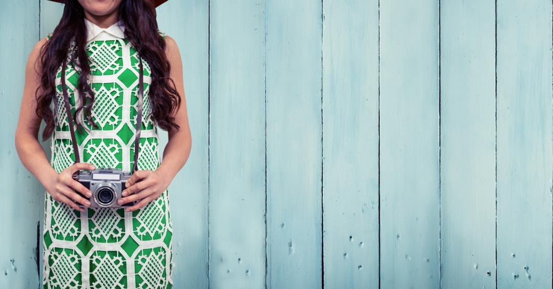 Image of a woman in a green dress standing against a fence holding a vintage camera
