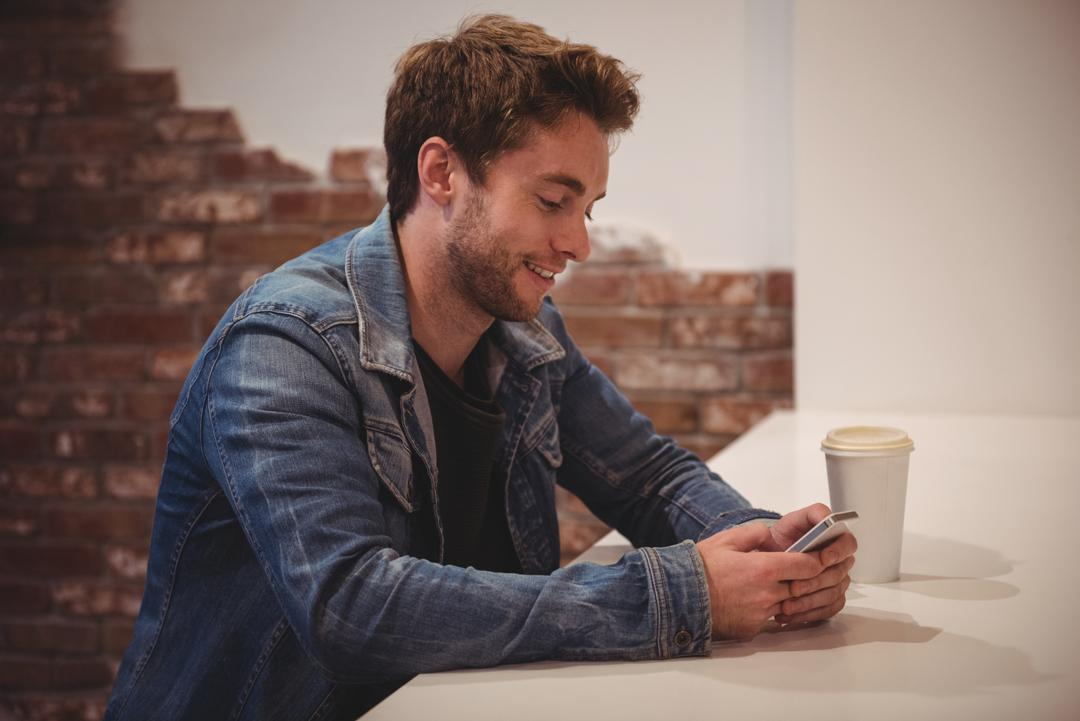 Man using mobile phone at table in café