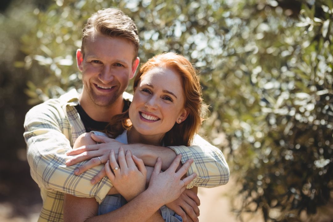 Portrait of happy couple embracing by trees at olive farm Free Stock Images from PikWizard