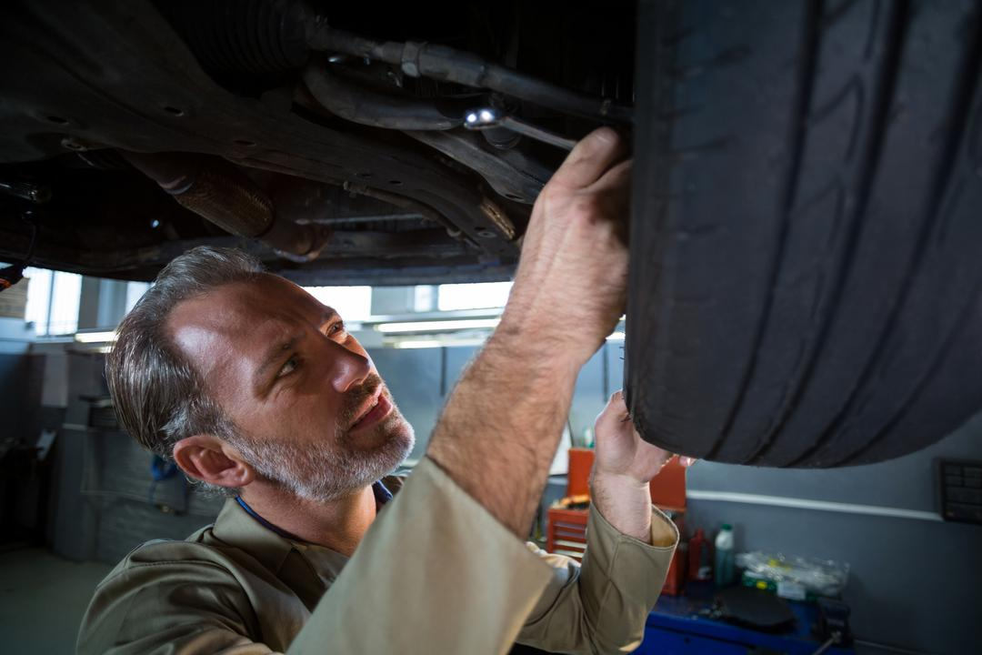 Mechanic examining a car in repair shop