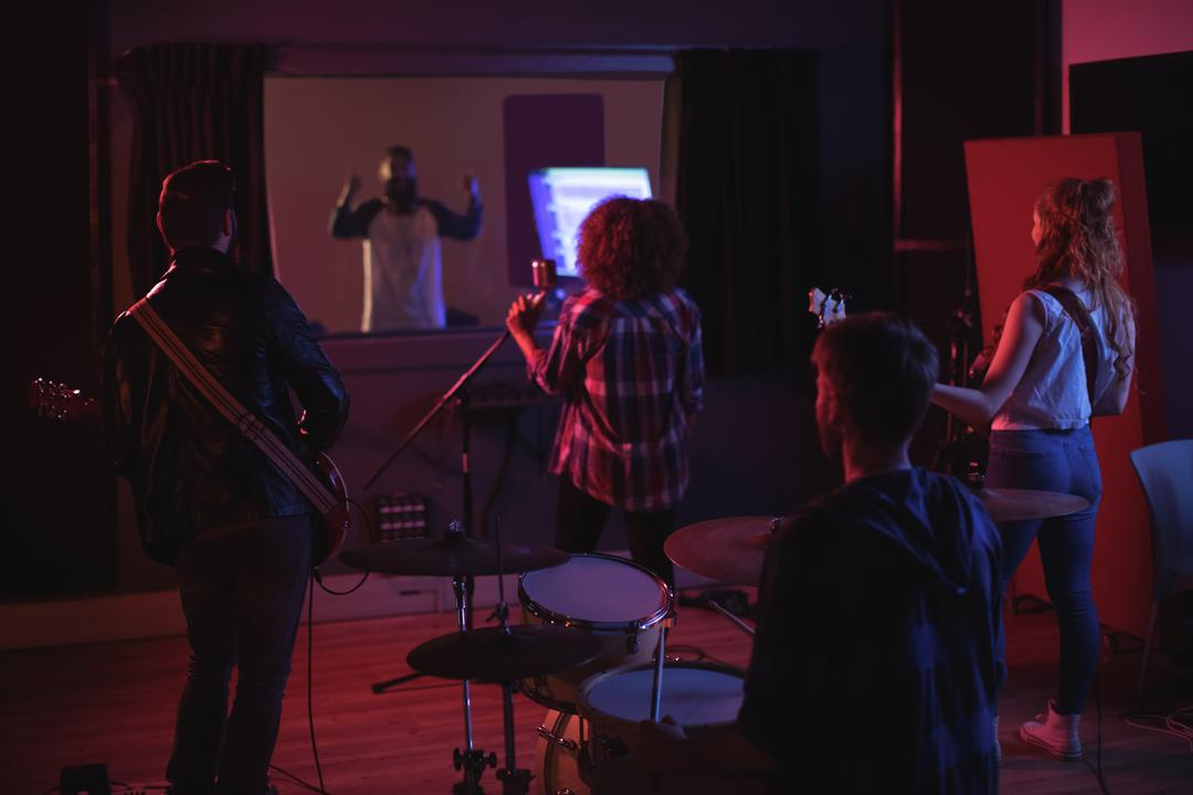 Rear view of band performing in recording studio
