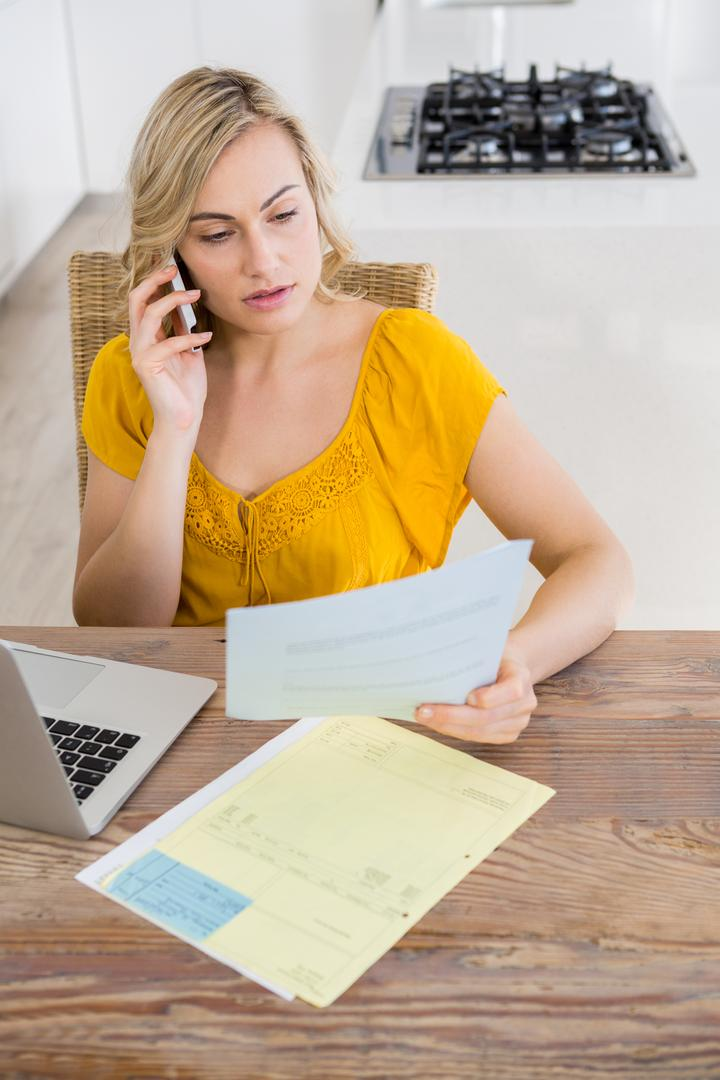 Woman talking on mobile phone while looking at bill in kitchen at home
