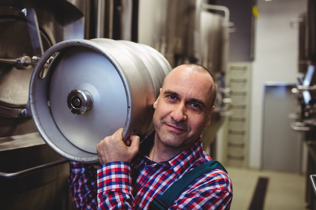 Portrait of male manufacturer carrying keg in brewery Free Stock Images from PikWizard