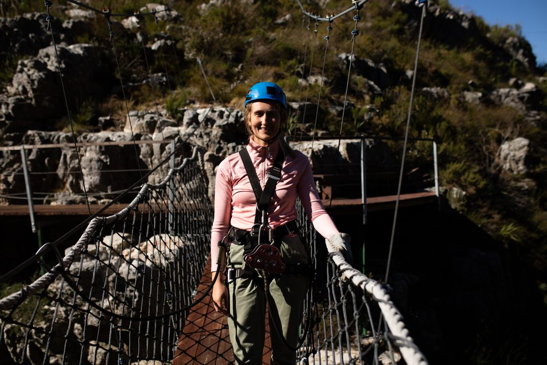 Portrait of a Caucasian woman enjoying time in nature, wearing zip lining equipment, smiling to camera on a sunny day in mountains. Fun adventure vacation weekend. Free Stock Images from PikWizard
