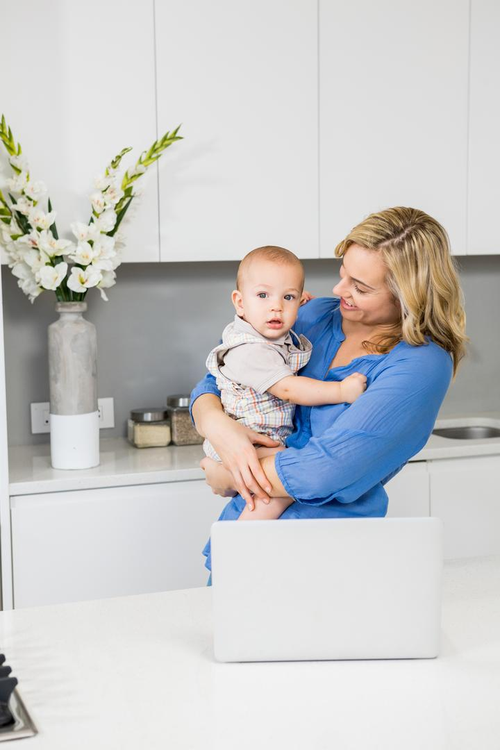 Mother and baby boy using laptop in kitchen at home