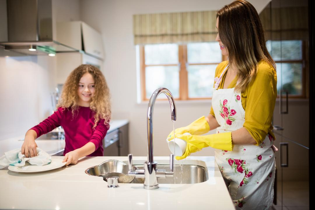 Mother assisting daughter in washing plate in kitchen at home