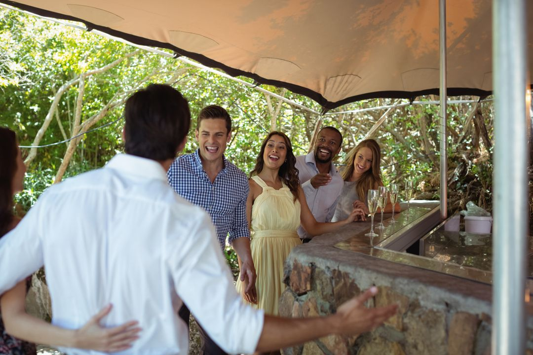 Smiling friends interacting while having a champagne at counter in restaurant Free Stock Images from PikWizard