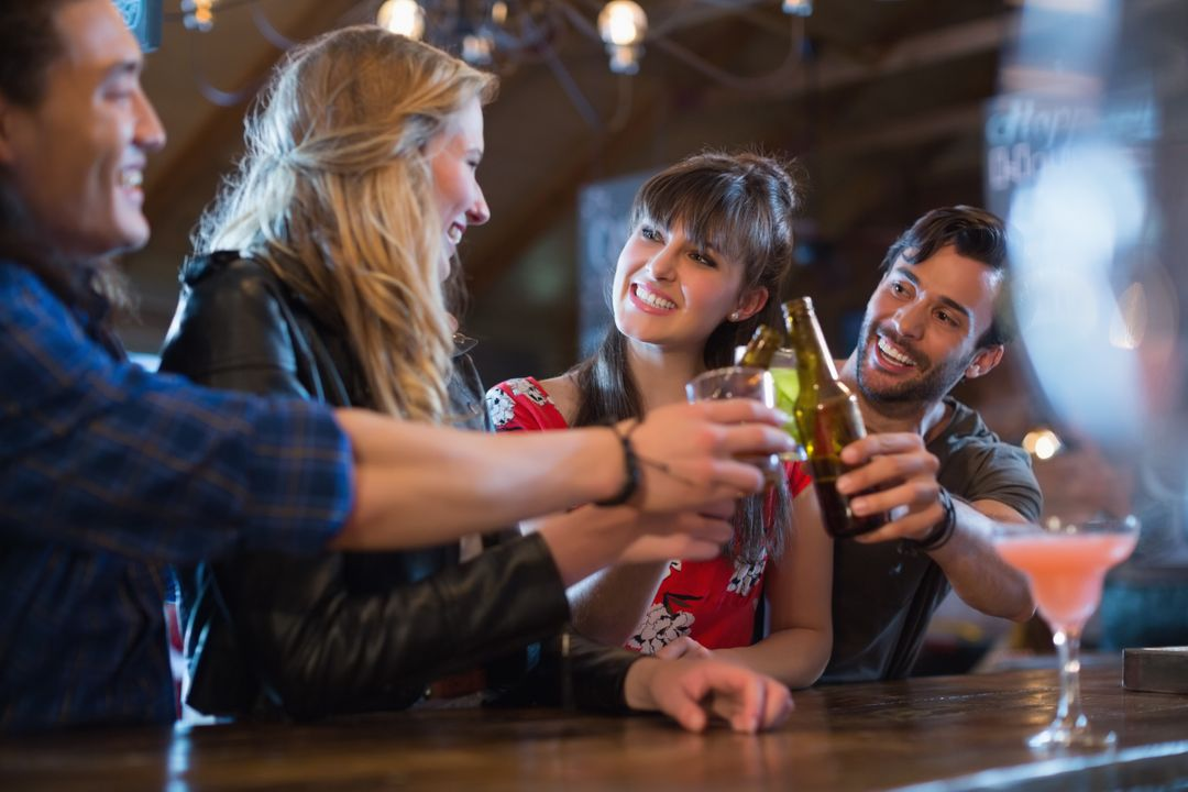 Cheerful friends toasting drinks at bar counter in pub
