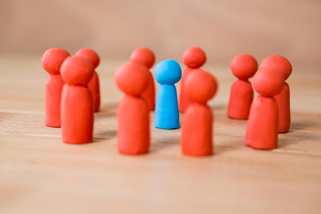 Conceptual image of blue figurine standing between a group of red figurines