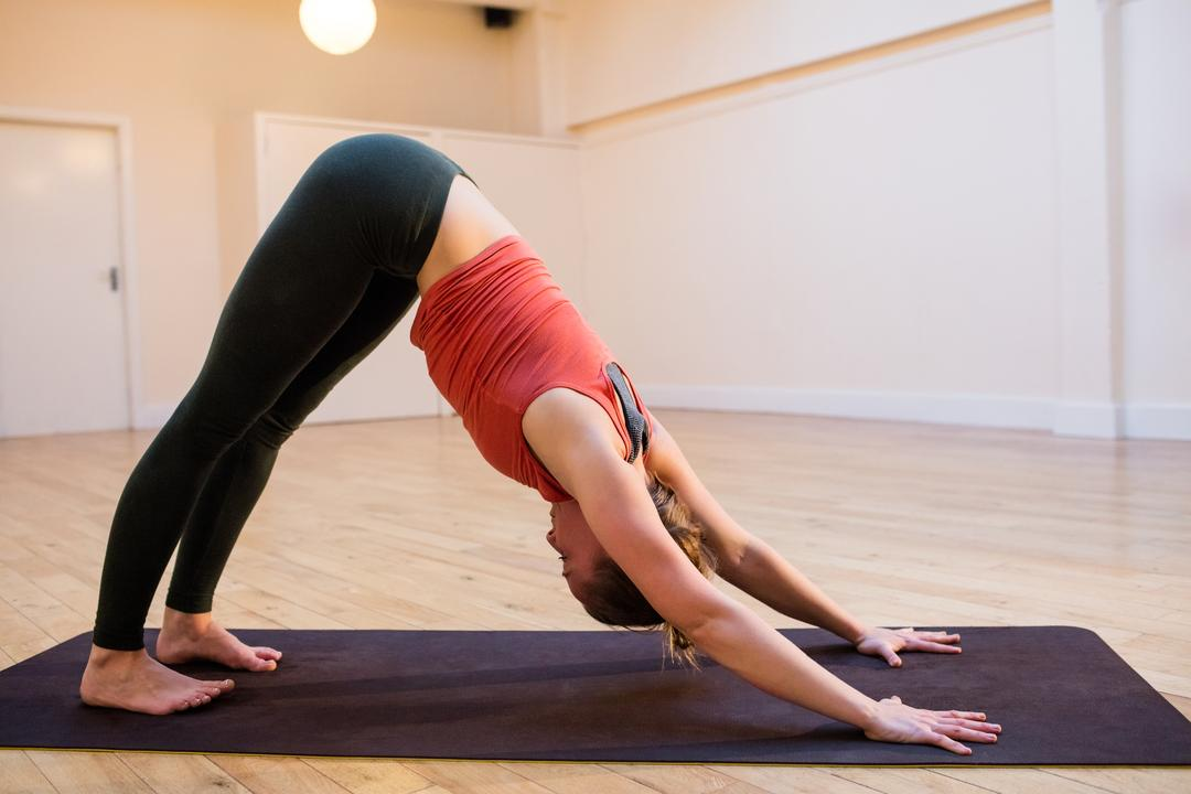 Woman performing yoga exercise on exercise mat in fitness studio