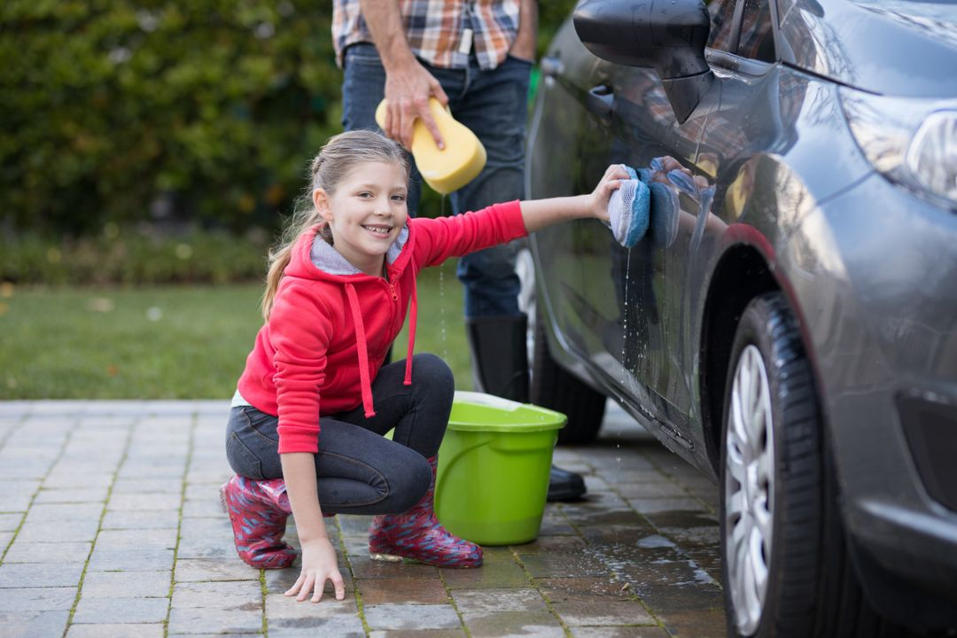 Portrait of teenage girl washing a car on a sunny day Free Stock Images from PikWizard