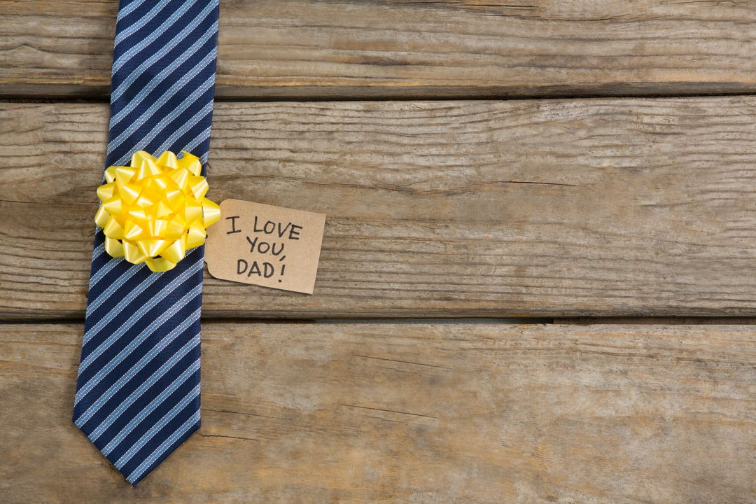 Overhead view of necktie with greetings on wooden table