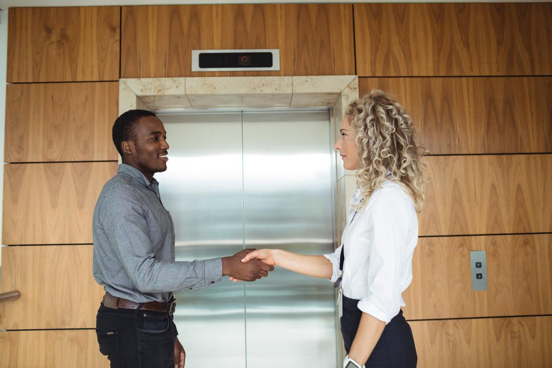 Business executives shaking hands near lift in office