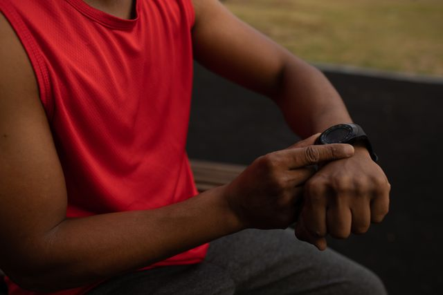 Mid section of mixed race man wearing sportswear checking his smartwatch, taking a break from running workout. Fitness outdoor healthy lifestyle.