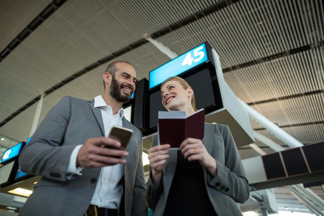 Business people holding boarding pass and using mobile phone in airport terminal