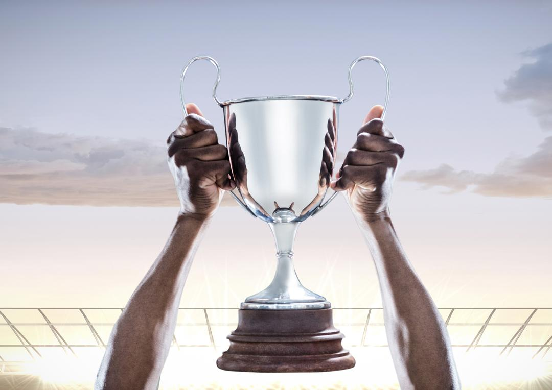 Hands holding champions trophy against stadium in background Free Stock Images from PikWizard