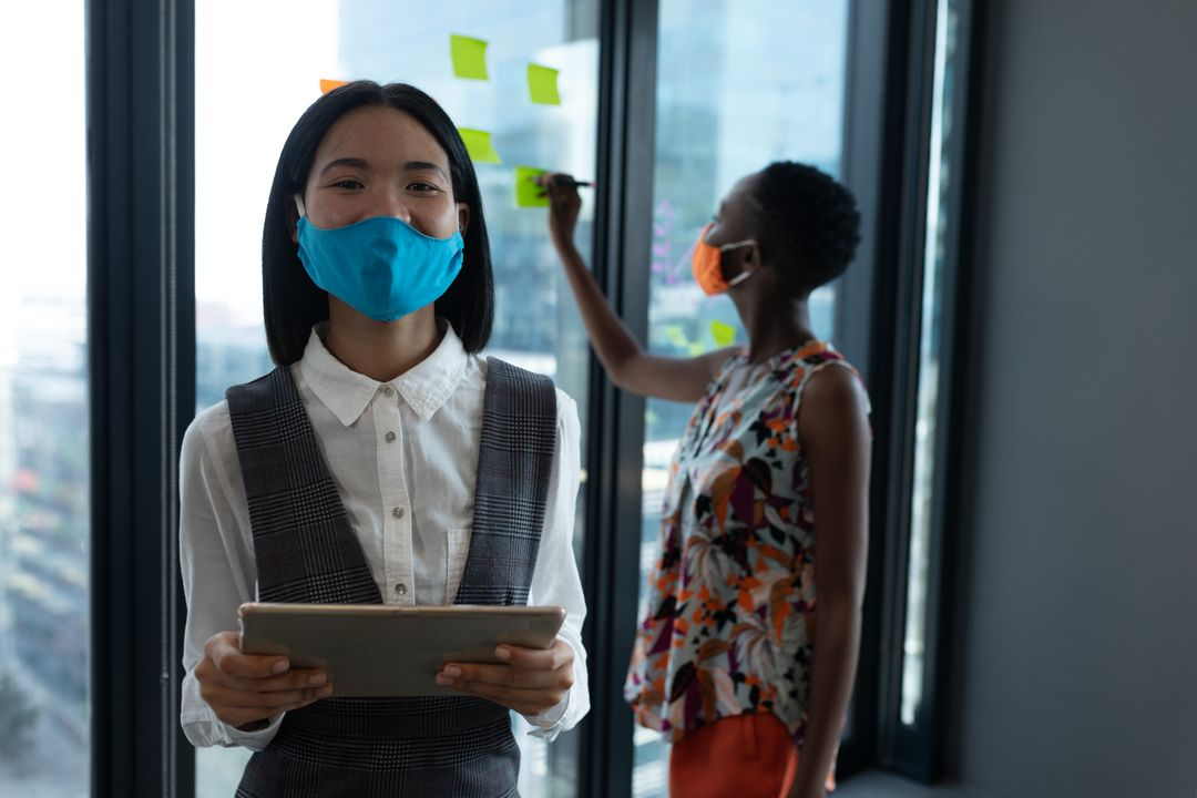 Asian woman wearing face mask using digital tablet looking at camera. With coworker in the background. Health and hygiene in creative office during coronavirus covid 19 pandemic. Free Stock Images from PikWizard