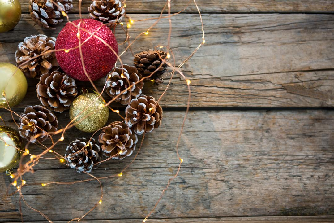 Close-up of rice lights, bauble ball and pine cone on wooden plank during christmas time Free Stock Images from PikWizard
