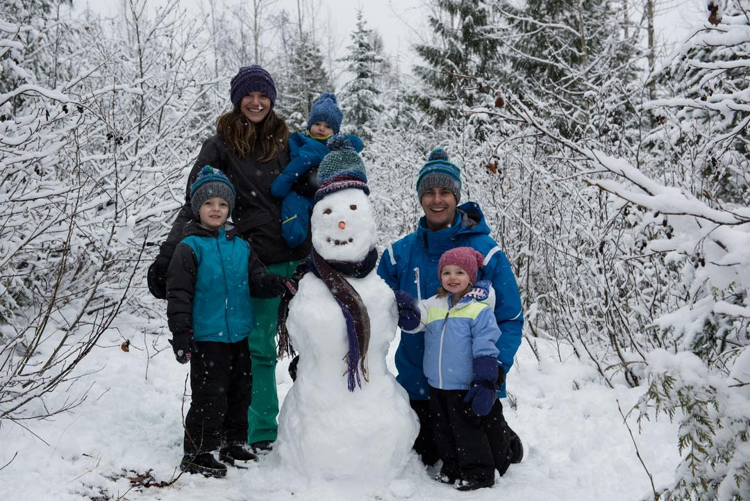 Portrait of happy family standing by snowman on beautiful snowy day
