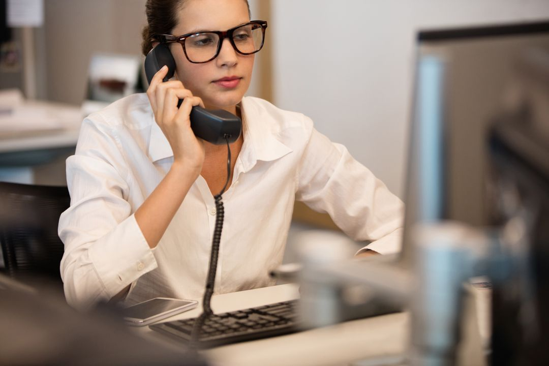Businesswoman using telephone while sitting at desk in office Free Stock Images from PikWizard