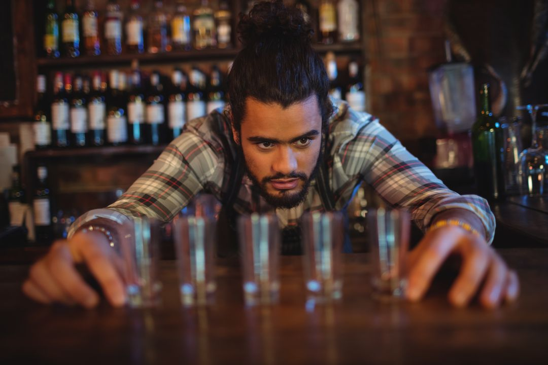 Waiter placing shot glasses in a row on counter in pub